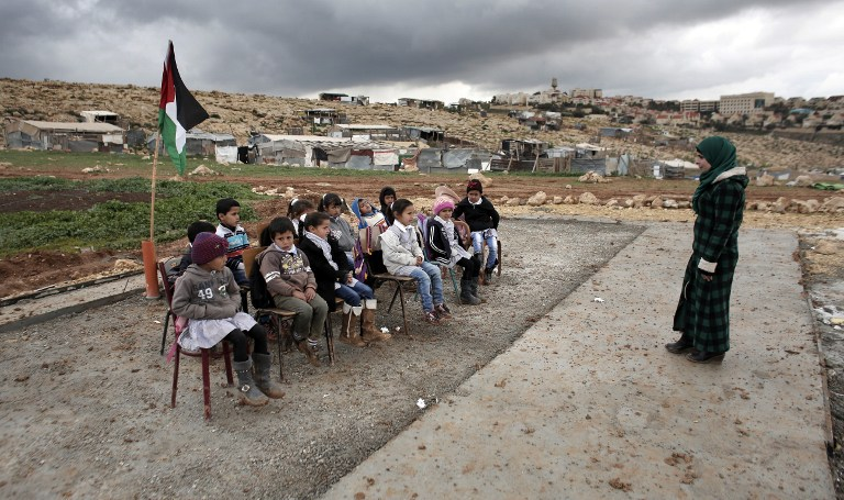 A Palestinian teacher leads a class of Palestinian Bedouin children from the Abu Anwar community near the Jewish settlement of Maale Adumim (background), in the West Bank city of al-Azariya, east of Jerusalem, on February 23, 2016. (AFP / AHMAD GHARABLI)
