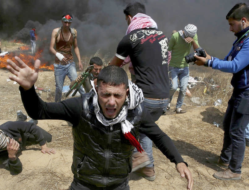 Palestinian protesters fall down from teargas fired by Israeli troops during a protest at the Gaza Strip's border with Israel on April 27, 2018.