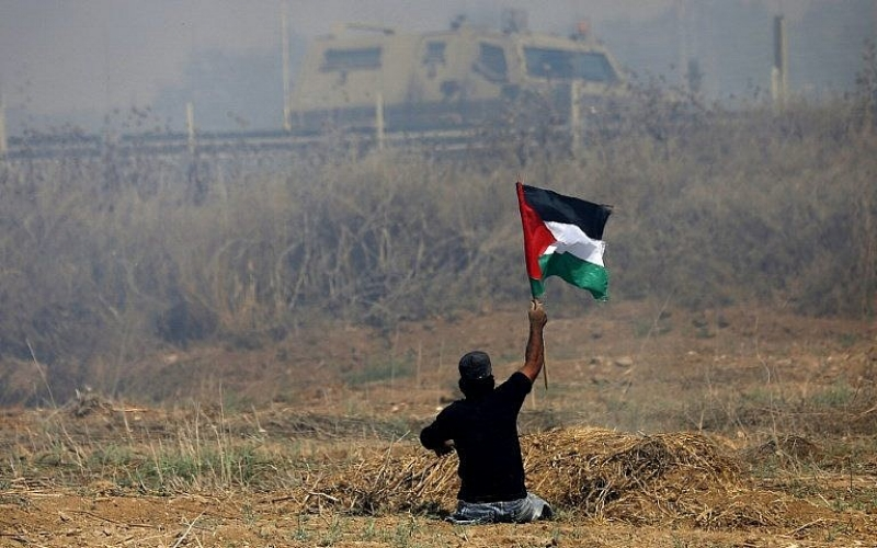 Palestinian demonstrator Ibrahim Abu Thurayeh, who lost his legs in a 2008 Israeli airstrike, waves a Palestinian flag during clashes with Israeli soldiers near the border fence east of Gaza City, May 19, 2017. (AFP Photo/Mohammed Abed/File) Abu Thurayeh was killed by an Israeli soldier December 15, 2017.