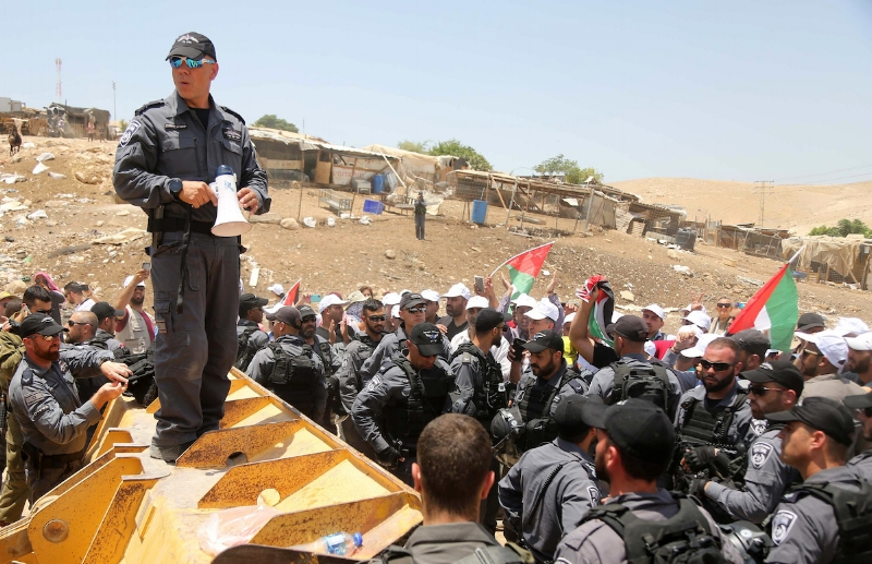 Israeli policemen scuffle with Palestinian demonstrators in the Bedouin village of al-Khan al-Ahmar east of Jerusalem in the occupied West Bank on July 4, 2018. Residents and activists voiced concern today that Israel is set to raze a Bedouin village in a strategic part of the occupied West Bank ignoring international calls for a reprieve. Activists said the Israeli military issued a warrant to the 173 residents of Khan al-Ahmar on Tuesday authorising it to seize access roads to the village. Photo by Shadi Hatem
