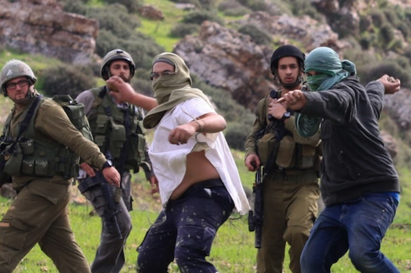 Israeli settlers throw stones at Palestinians in front of Israeli soldiers who watch without intervening.