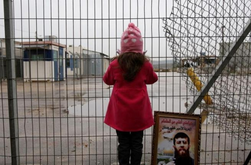 Maali, daughter of prisoner Khader Adnan, stands next to a picture of her father outside a prison. (AFP/Abbas Momani)