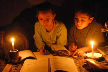 Palestinian students do homework by candlelight.