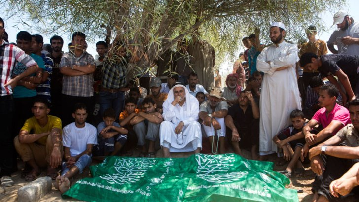 Members of the Abu Jameh family gather in the cemetery to mourn their loved ones. 24 family members were killed in an attack on July 20, 2014.