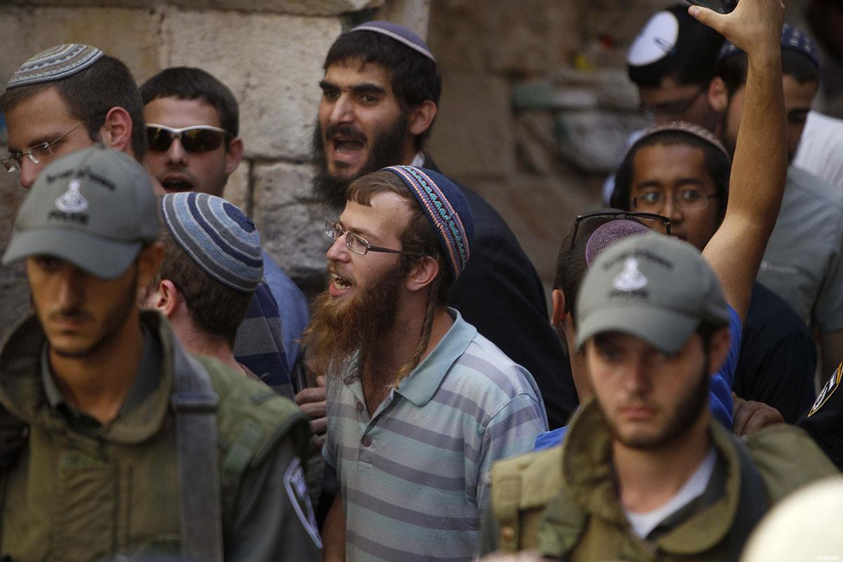 Israeli settlers, guarded by Israeli forces [File photo]