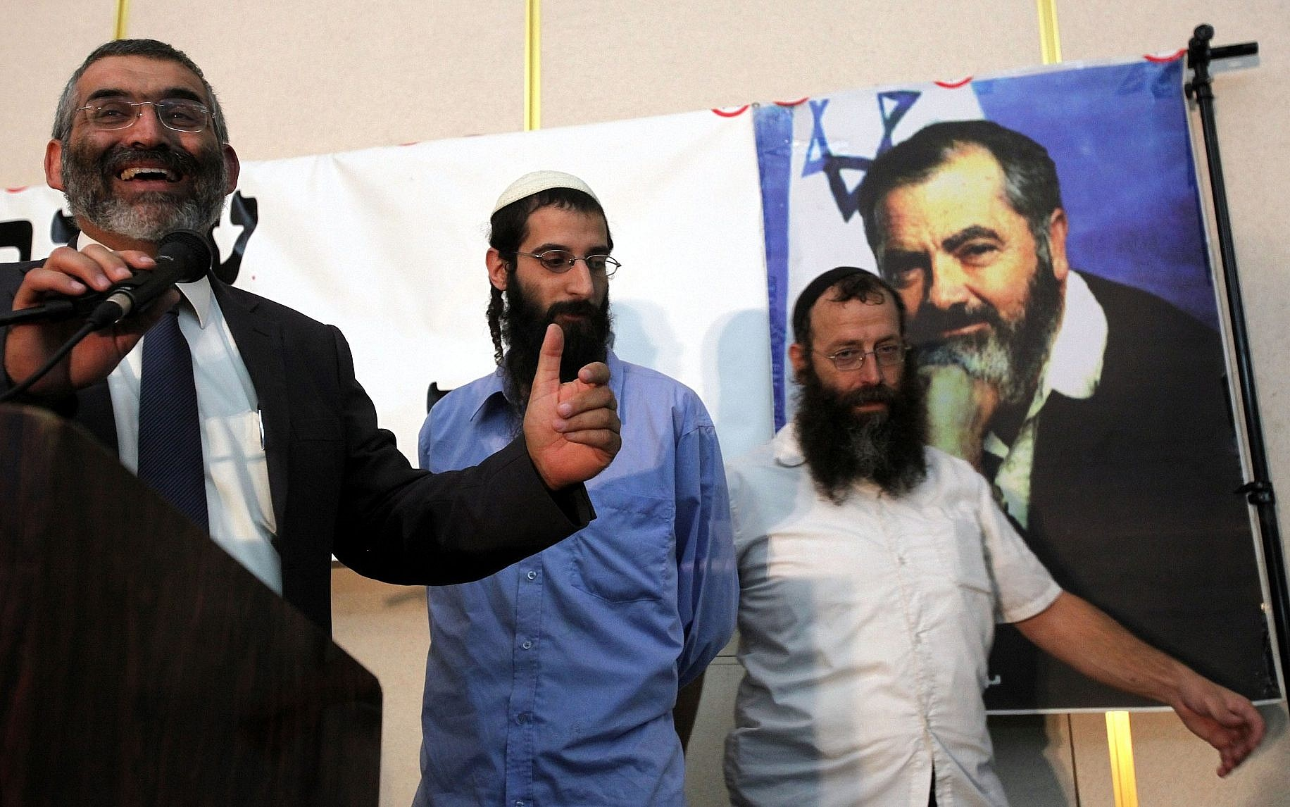 Michael Ben Ari (left) speaks during a ceremony honoring the late Jewish extremist leader Rabbi Meir Kahane in a Jerusalem hall, October 26 2010. At right is Baruch Marzel (Yossi Zamir / Flash 90)