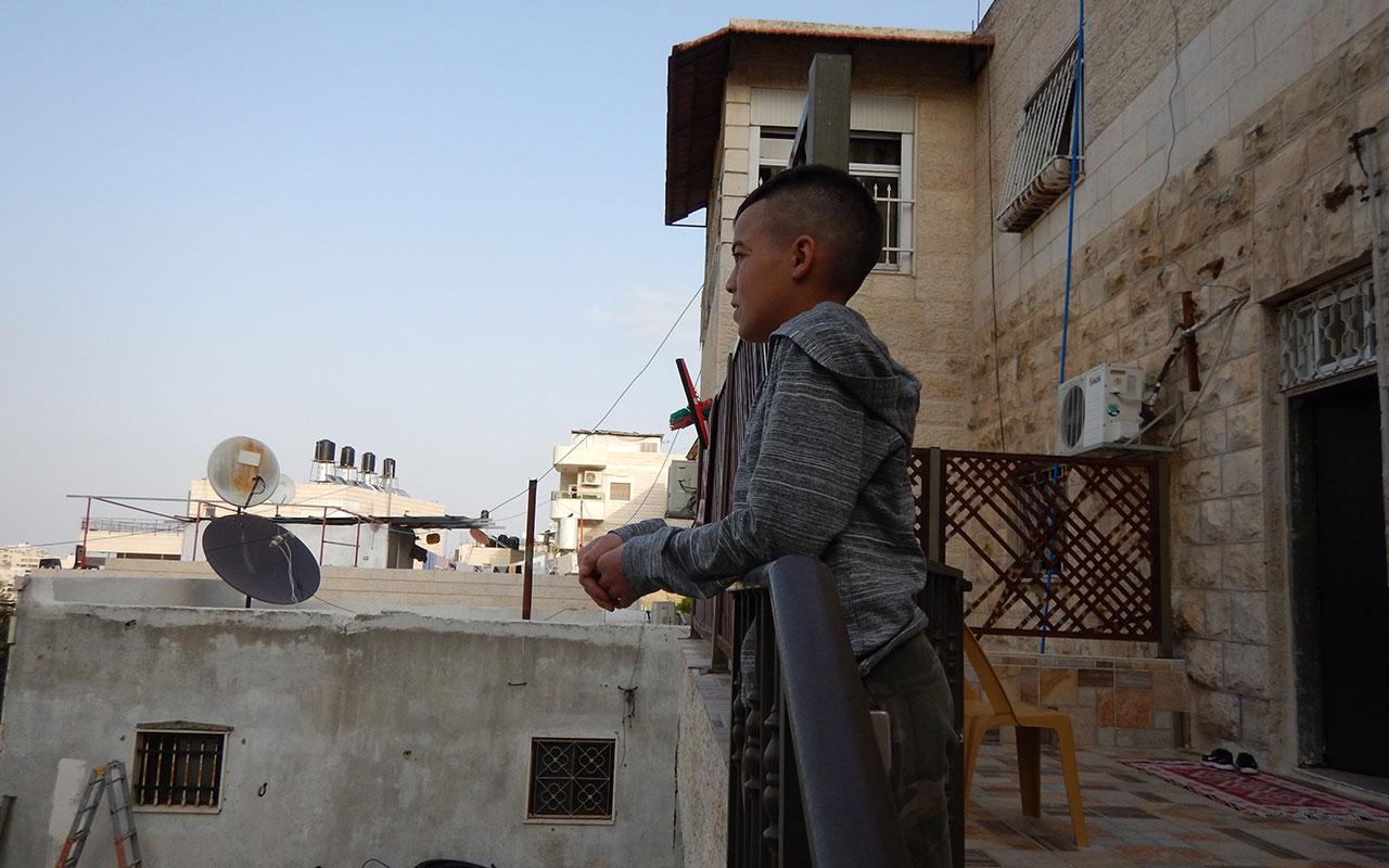 Adam Abu Ryalah on a balcony in his home in Al-Eisawiyah, East Jerusalem (Photo by 'Amer 'Aruri, B'tselem)