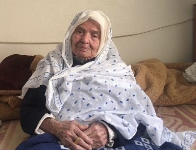 Halima Abudayya, 95, sitting on her bed in her son's house in northern Gaza, dreams of returning to her true home (MEE/Maha Hussaini)