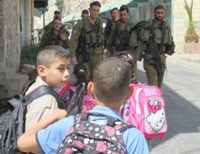 Palestinian children on their way home from school encounter a group of Israeli soldiers at the bottom of the school steps