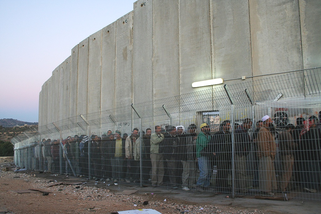 Men and women from all over the Southern West Bank stand in line for hours each morning on their way to work outside of Bethlehem. Photo by delayed gratification.