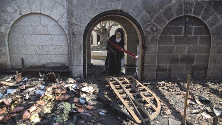 A nun inspects the damage at the Church of the Multiplication at Tabgha, Ariel Schalit/AP