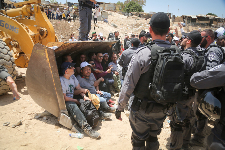 Israeli policemen confront Palestinian demonstrators in the Bedouin village of Khan al-Ahmar, east of Jerusalem, on July 4, 2018. (Flash90)