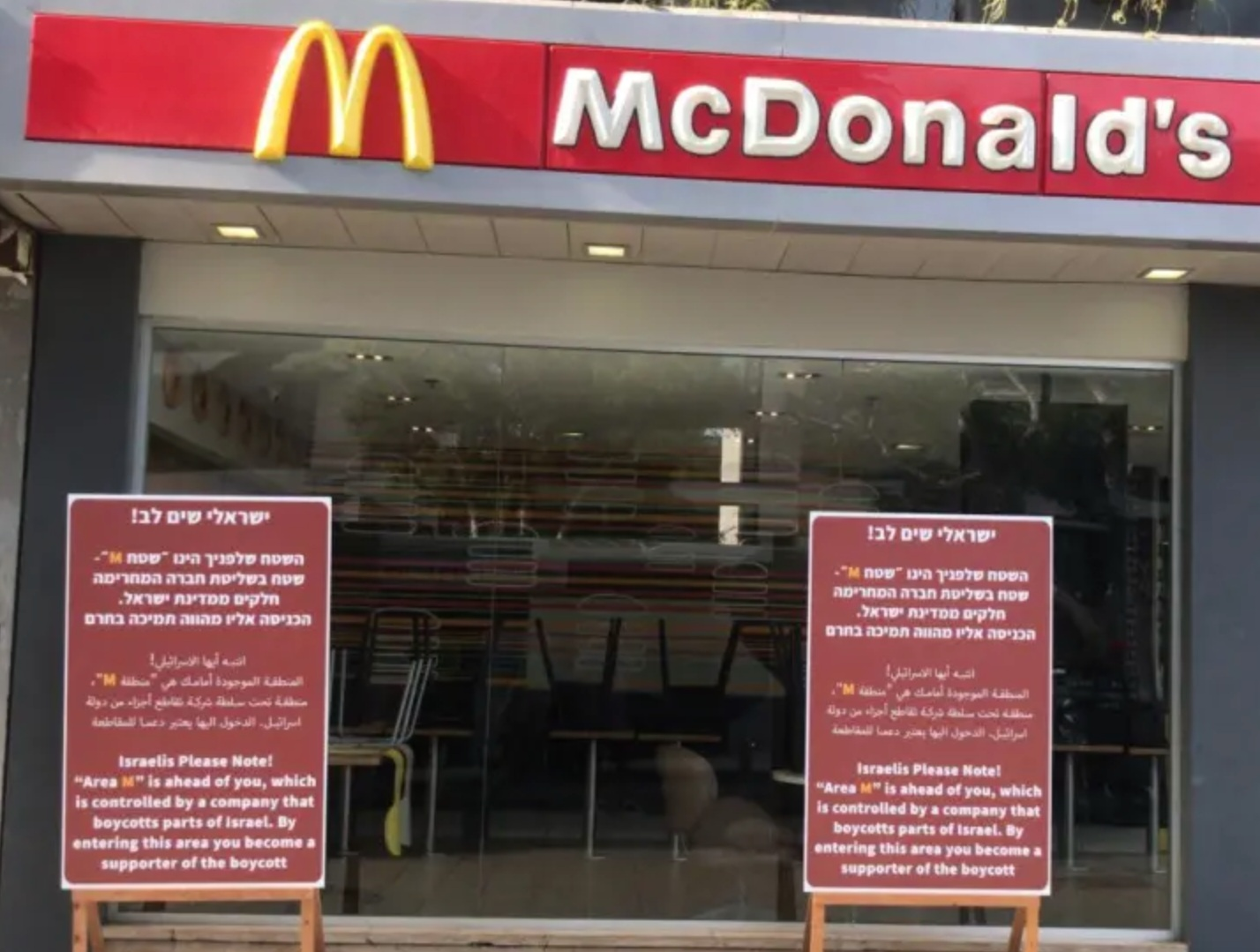 Signs outside a McDonald's in Tel Aviv protest the refusal of the local franchise to open in Judea and Samaria.. (photo credit: MAARIV)