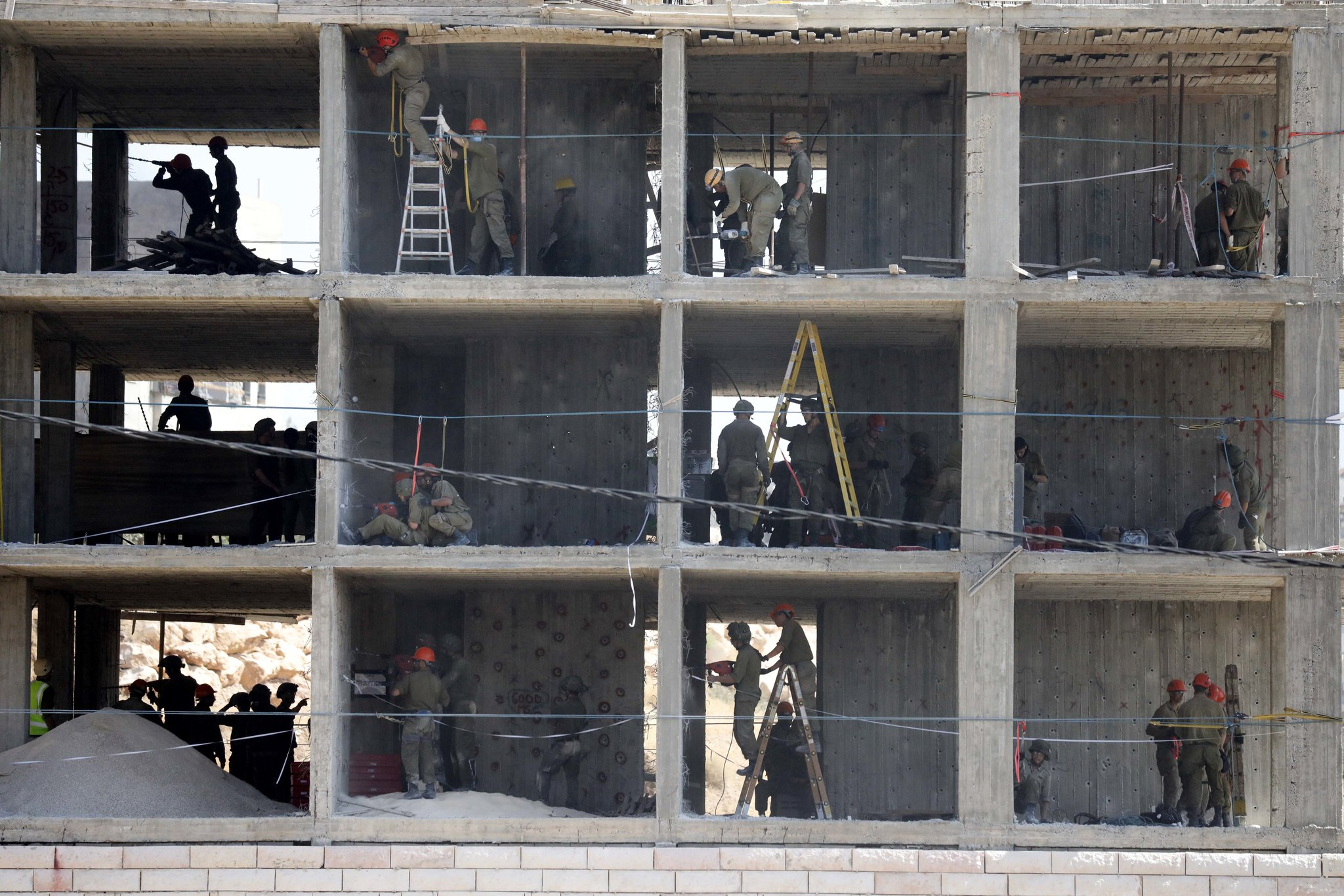 Israeli soldiers place explosives to demolish a building in Sur Baher, in East Jerusalem [Abed Al Hashlamoun/EPA]