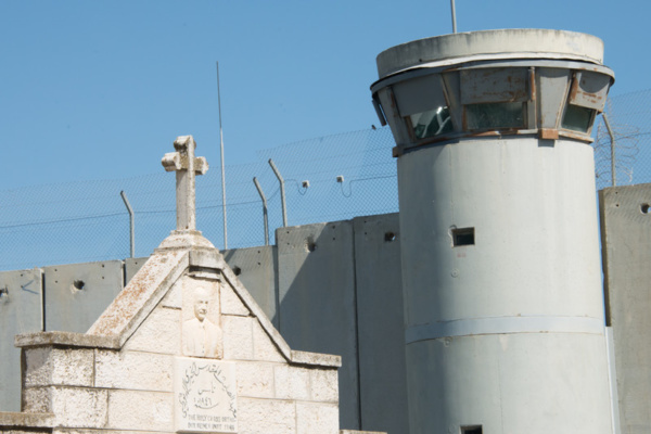 A stone cross appears on a Palestinian building near the Israeli separation wall dividing the West Bank town of Bethlehem, April 29, 2014. (credit: Ryan Rodrick Beiler)