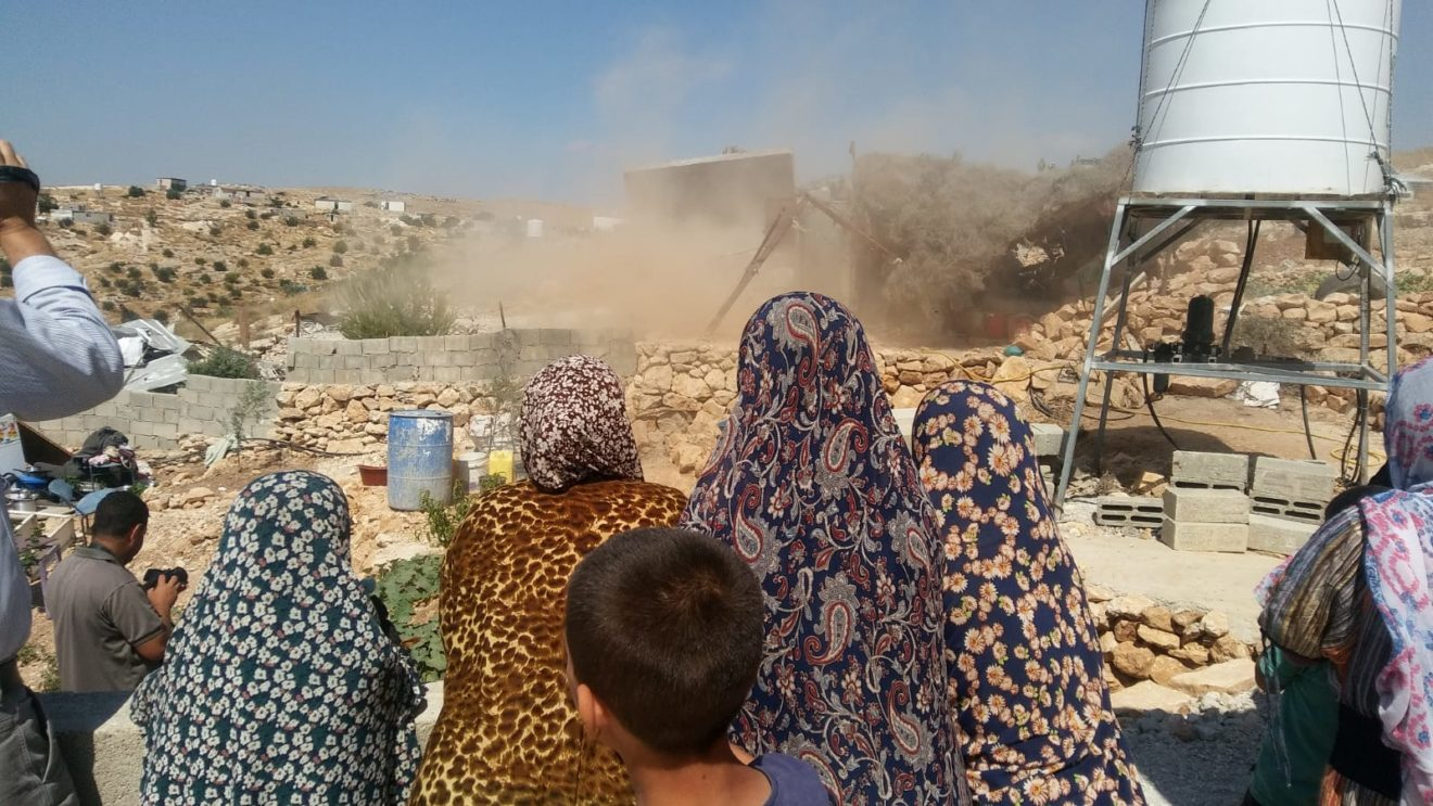 The al Dababsh family watches as their home is razed to the ground in the village of Khalet al Dabeh
