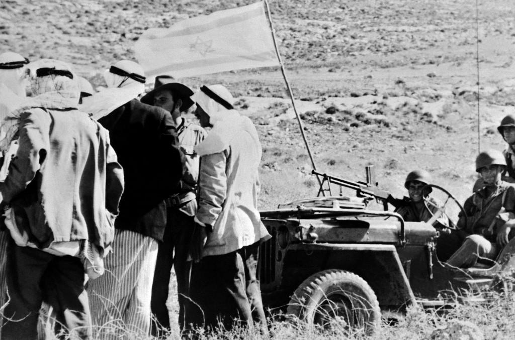 Palestinians speak with Israeli soldiers by a captured Arab village in 1948 (AFP)