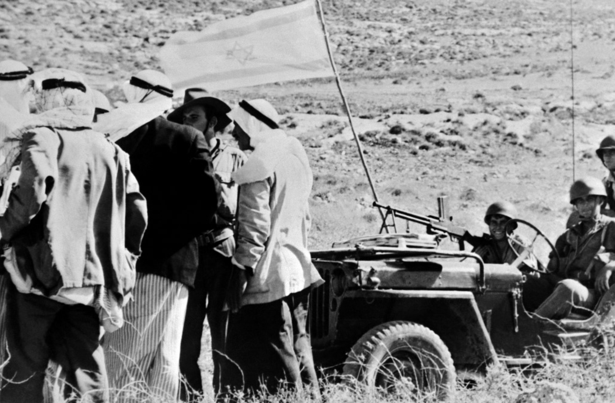 Palestinians speak with Israeli soldiers by a captured Arab village in 1948 (AFP)