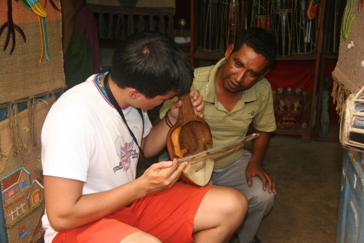 Anthony learning Nepali musical instrument