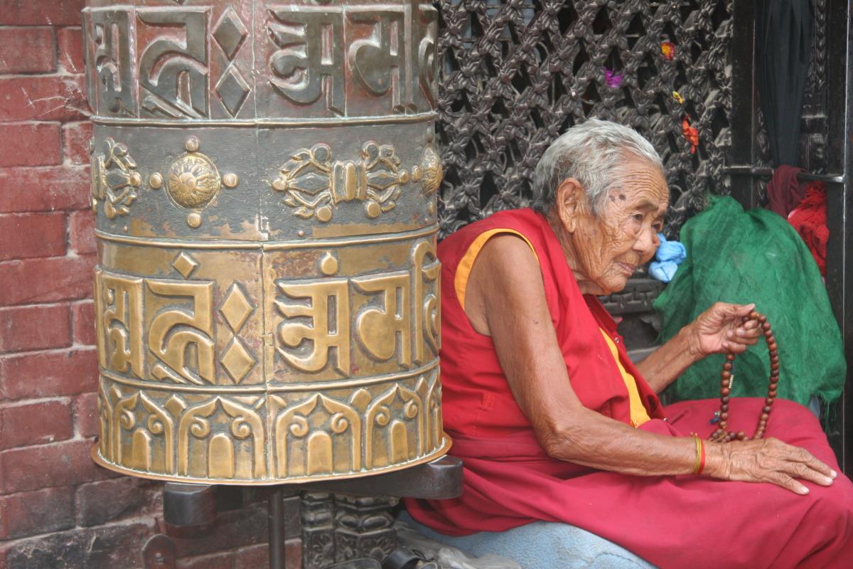 Old Tibetan monk and prayer wheel
