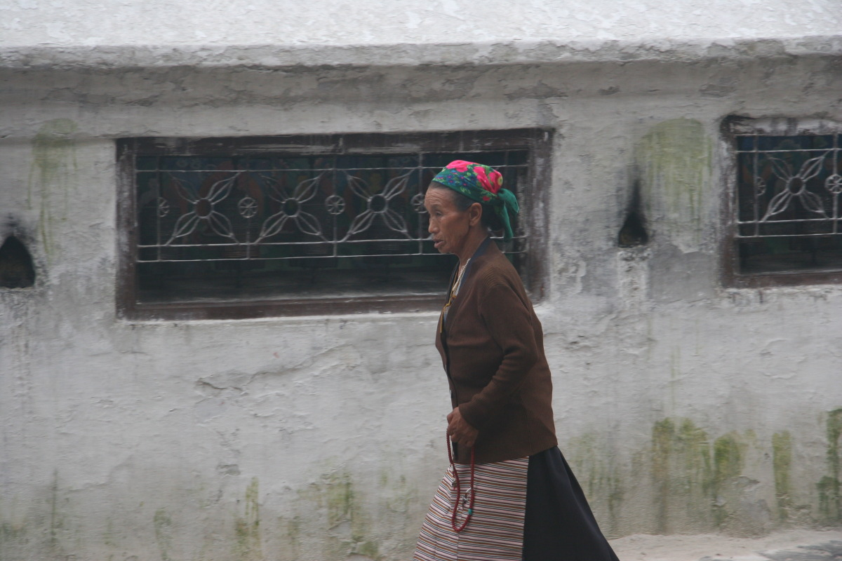 Tibetan woman and prayer wheels around base of Boudhinath stupa