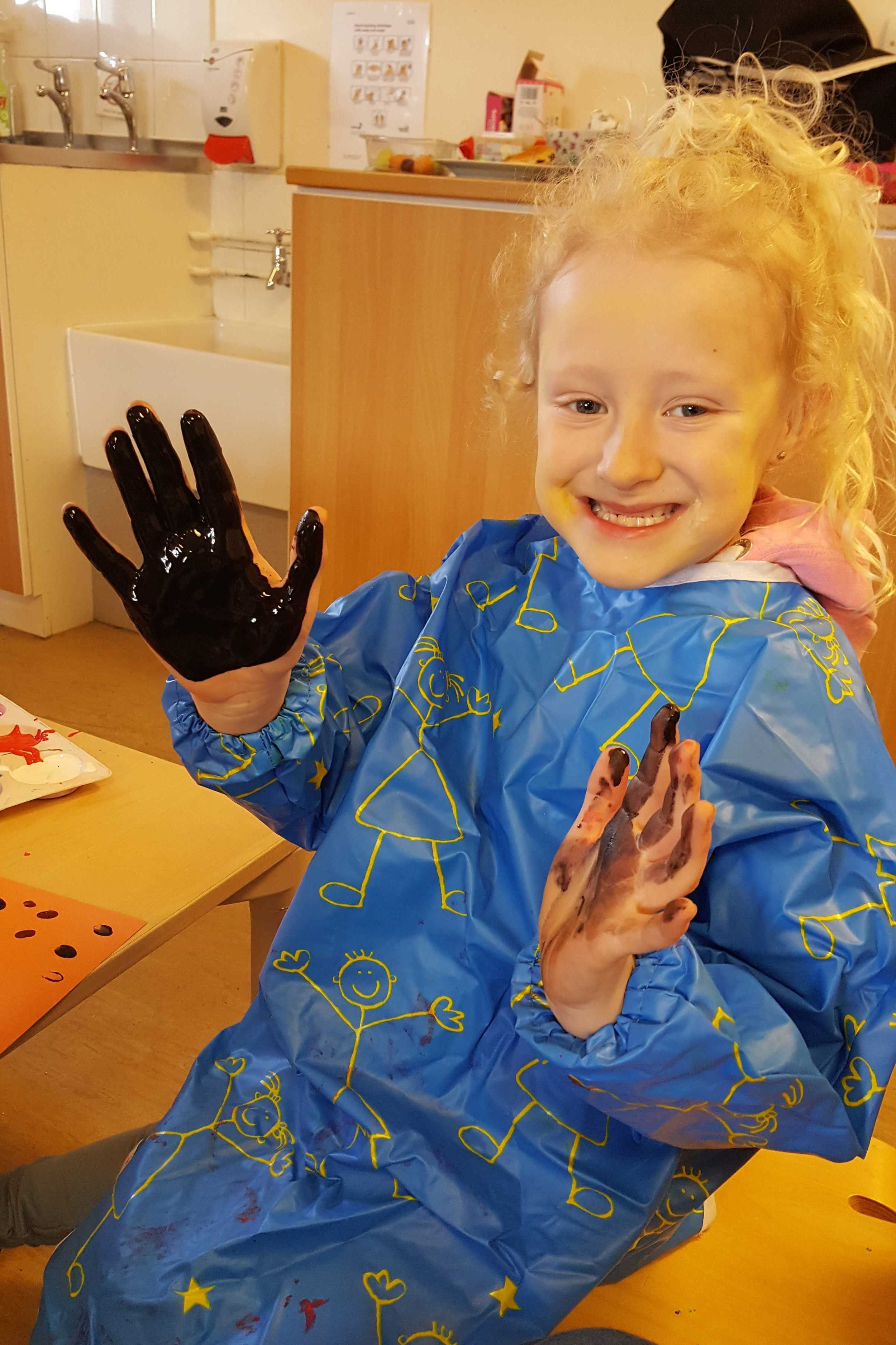Evie (year 1) enjoying hand painting.