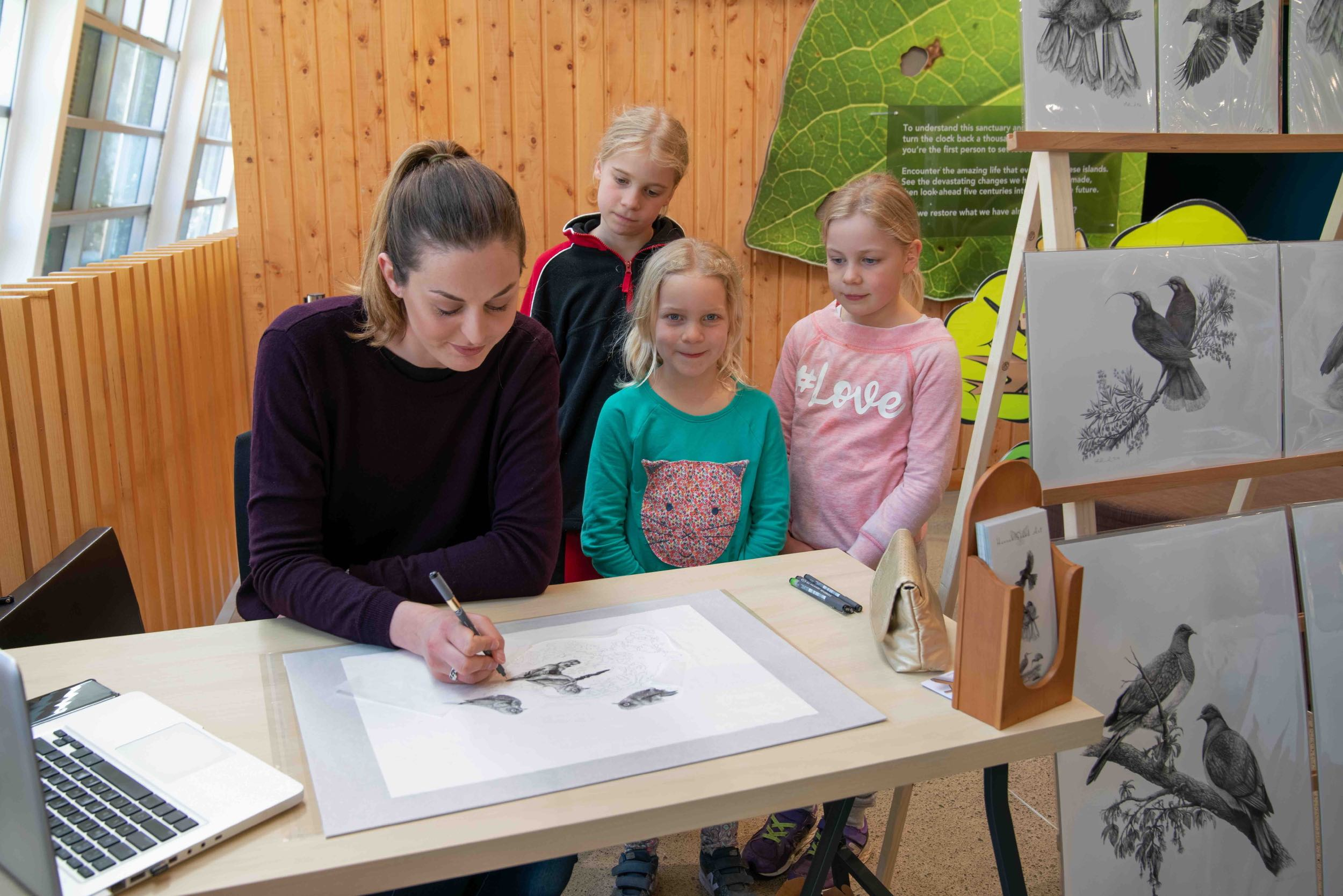 Hannah draws custom artwork, with Jusrine's girls watching. Photograph taken at live drawing event at Zealandia Ecosanctuary by   Judi Lapsley Miller   .