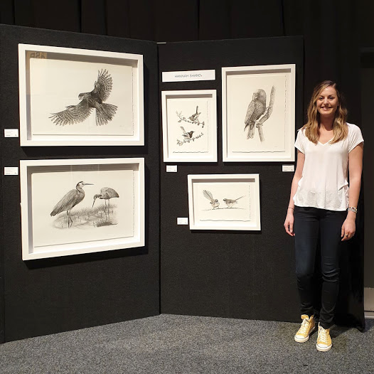 Hannah stands beside her display or original artworks at the show.