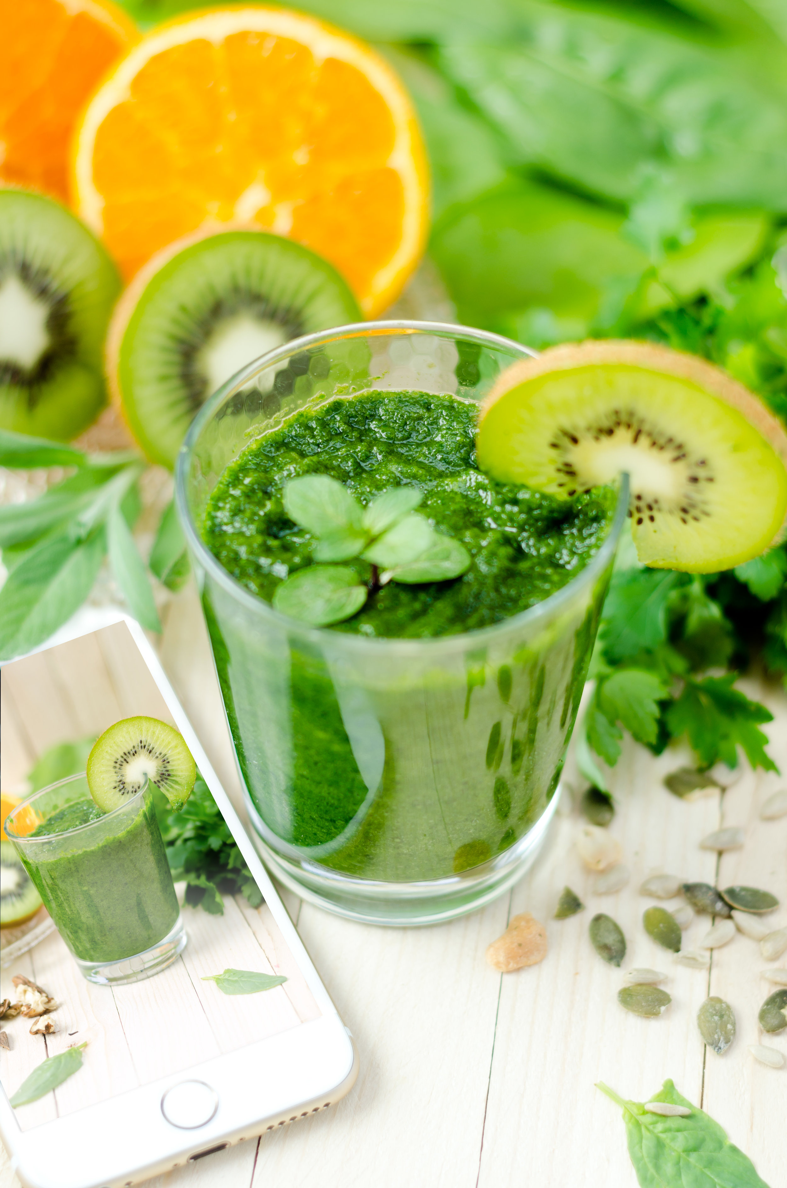 Healthy green smoothie with spinach, kiwi and orange and mobile