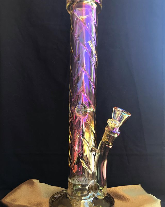 "@redeyetekpipes 15"" finish twist tube w/ honeycomb perc & ice catch🤤😍 Currently available here at the Fayetteville location in 2 different colors Remember each @redeyetekpipes piece comes with a super cute little sticker ! #futuristicglass #classyglass #stayglassy #irridescentglass #irridescentwaterpipe #redeyetekglass"