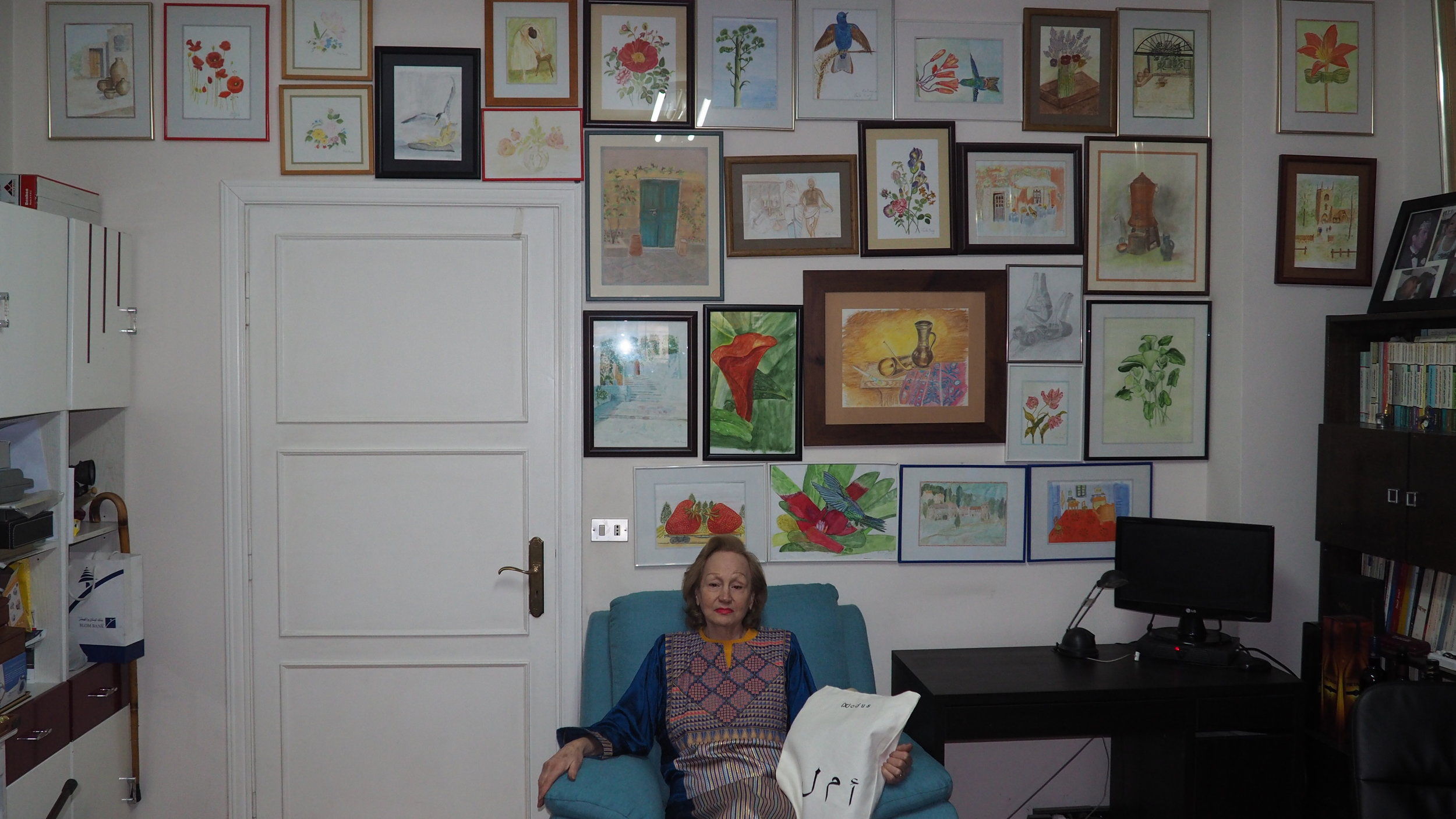 Leila sits in her private living room,in front of a collection of her own paintings.