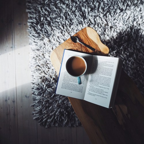 Cup-of-tea-and-an-open-book-on-a-coffee-table-on-a-grey-floor-with-a-slant-of-light.jpg
