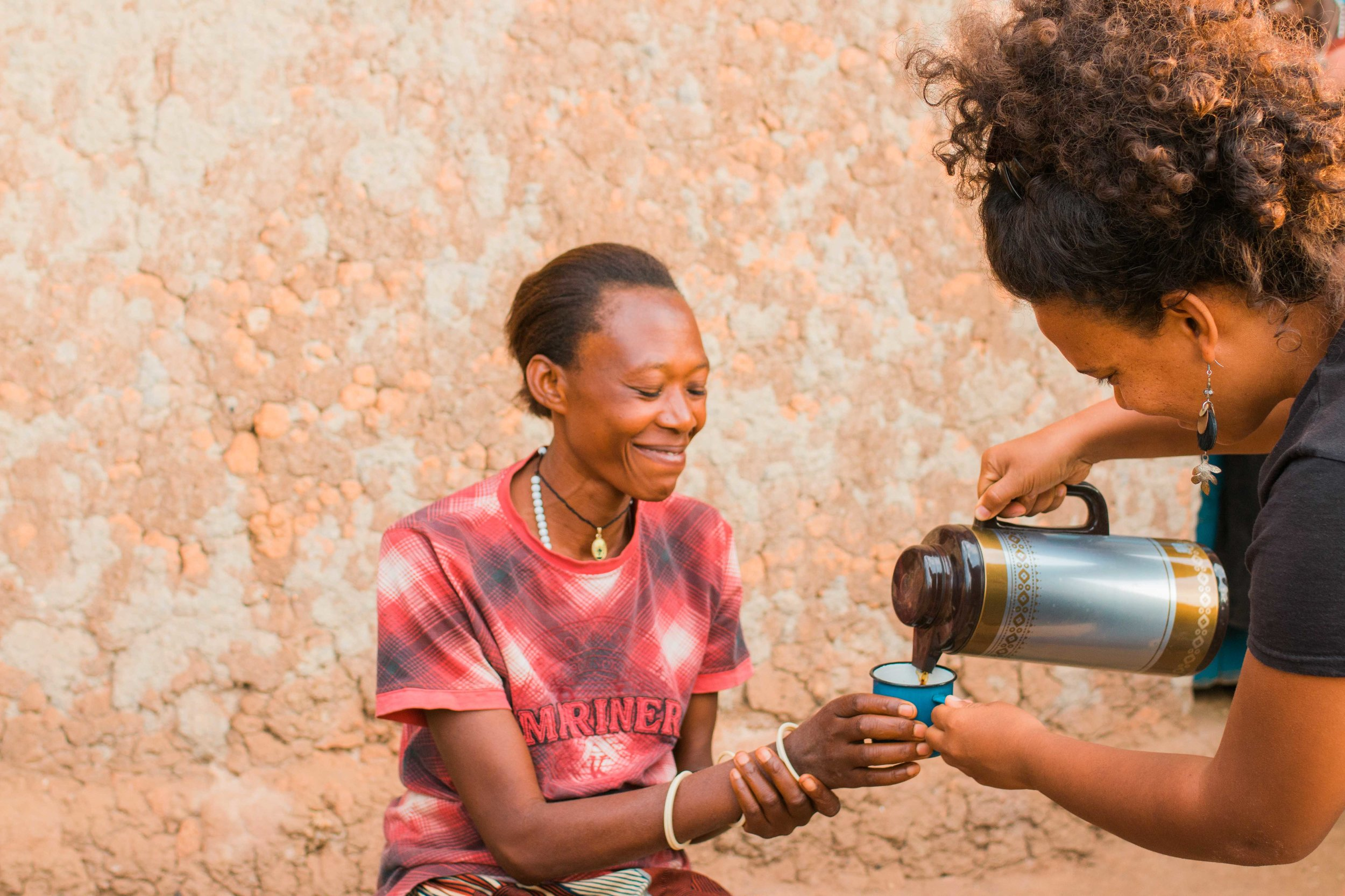 Dorothy of Gaharo Hill in Burundi being served her very first cup of coffee by Lauren, General Manager of Long Miles Coffee Project. Dorothy delivers coffee cherries to Long Miles' Bukeye washing station.