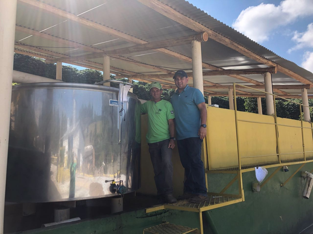 """Ivan Solis, fermentation and processing expert from Costa Rica, and Alessandro """"Viola"""", processing manager at Irmas Pereira with the adapted cheese making fermentation tank used for anaerobic processing on several Carmo Coffees farms."""