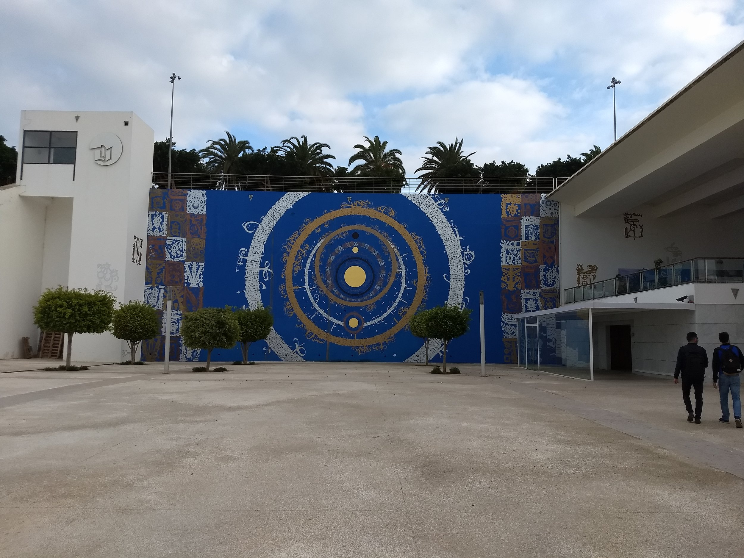 The library is set back from the road, on the other side of a large courtyard filled with sculptures and murals. Photo Credit: Liora Silkes, 2018.