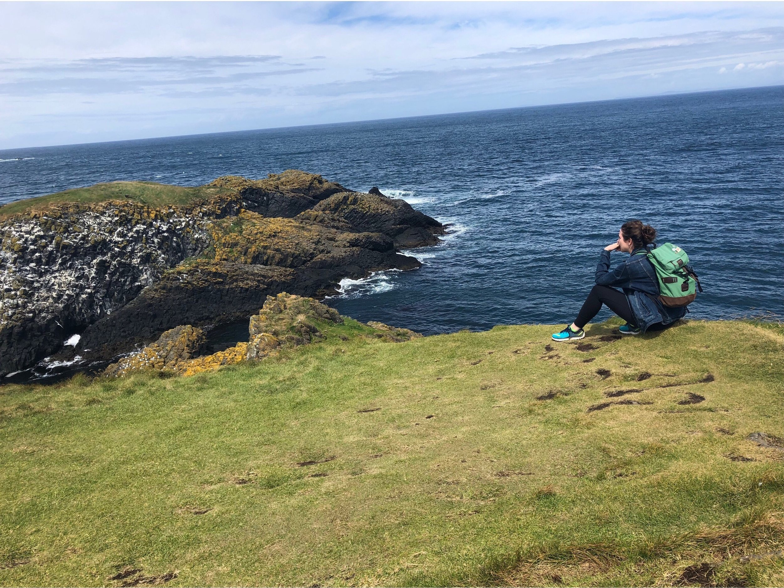 Sitting on a cliff by the sea in Northern Ireland. Photo Credit: Russ, 2018