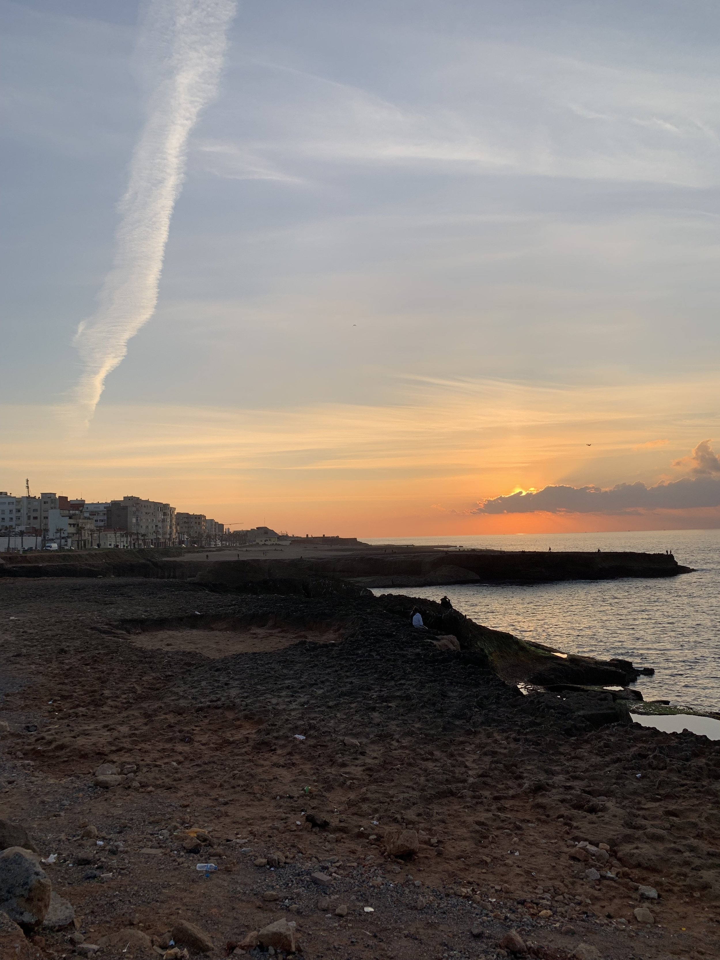 The sun sets on the Moroccan coast. As the sun slowly dips behind the clouds and past the horizon, the sunset ushers in the bustling Rabat nightlife. Photo Credit: M. Aboko-Cole, Spring 2019.