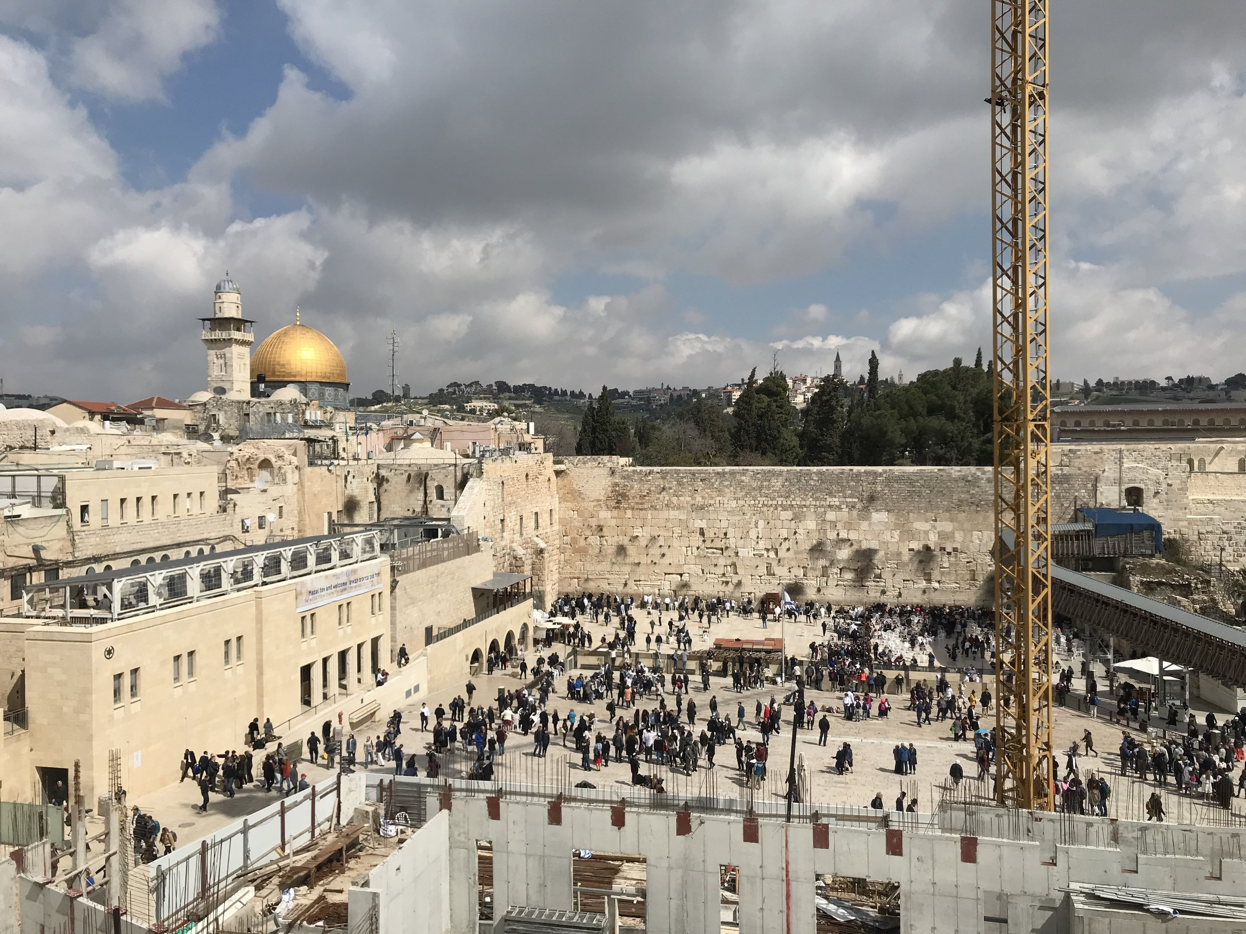 While in Israel for spring break, I was fortunate enough to be able to visit one of the most famous religious sites in the world: The Western Wall in Jerusalem. It is considered one of the holiest places in the world for Jewish people to pray and witnessing the multitude of people praying at its base was an unforgettable sight. In addition to the beauty of the sight, I was able to experience some cultural nuances such as some of those praying at the base of the wall walked backwards to exit the prayer space, not turning their backs on the wall. It is a breathtaking site with the golden Dome of the Rock, an Islamic shrine in the Old City of Jerusalem. The vantage point that this photo was taken from was included in a two-hour walking tour I did through the Old City and its four quarters: the Christian, Jewish, Muslim, and Armenian Quarters. Photo credit: Tenney, 2019