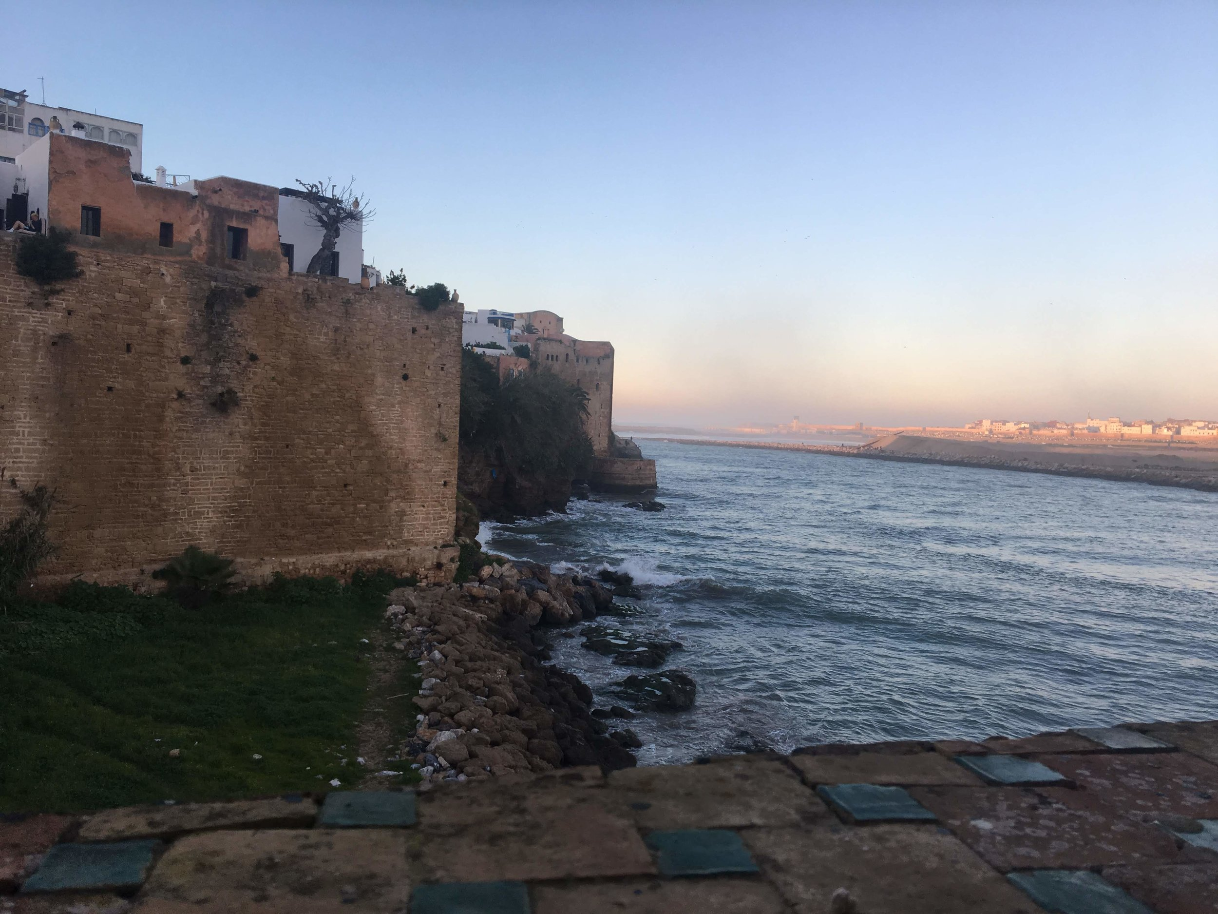In the Kasbah in Rabat, we sit and sip mint tea, watching the reflection of the sunset on the water. One of the most beautiful corners of Rabat, the Kasbah holds cats, tourists, and a spectacular view of the water. Photo credit: Fisher, 2019
