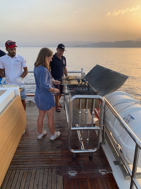 For 25 JD each, we got more than just a 2-hour boat ride at dinnertime: we also got dinner! Here, my friend Laurie was helping with the grilling. The total meal was a delicious mix of salads, meat, bread, and fish! Photo credit: Moriarty, 2019