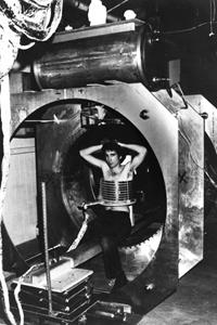 Lawrence Minkoff, PhD, post-graduate assistant, sitting in Raymond Damadian, MD's self-built  Indomitable  MRI machine for the acquisition of the first-ever MRI image of a human, July 3, 1977.