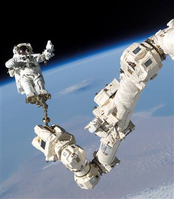 The Mobile Servicing System, also known as Canadarm2, is a 58-foot-long robotic system on board the International Space Station that plays a key role in station assembly and maintenance. In this photo, NASA astronaut Stephen Robinson rides Canadarm2 during a space mission.