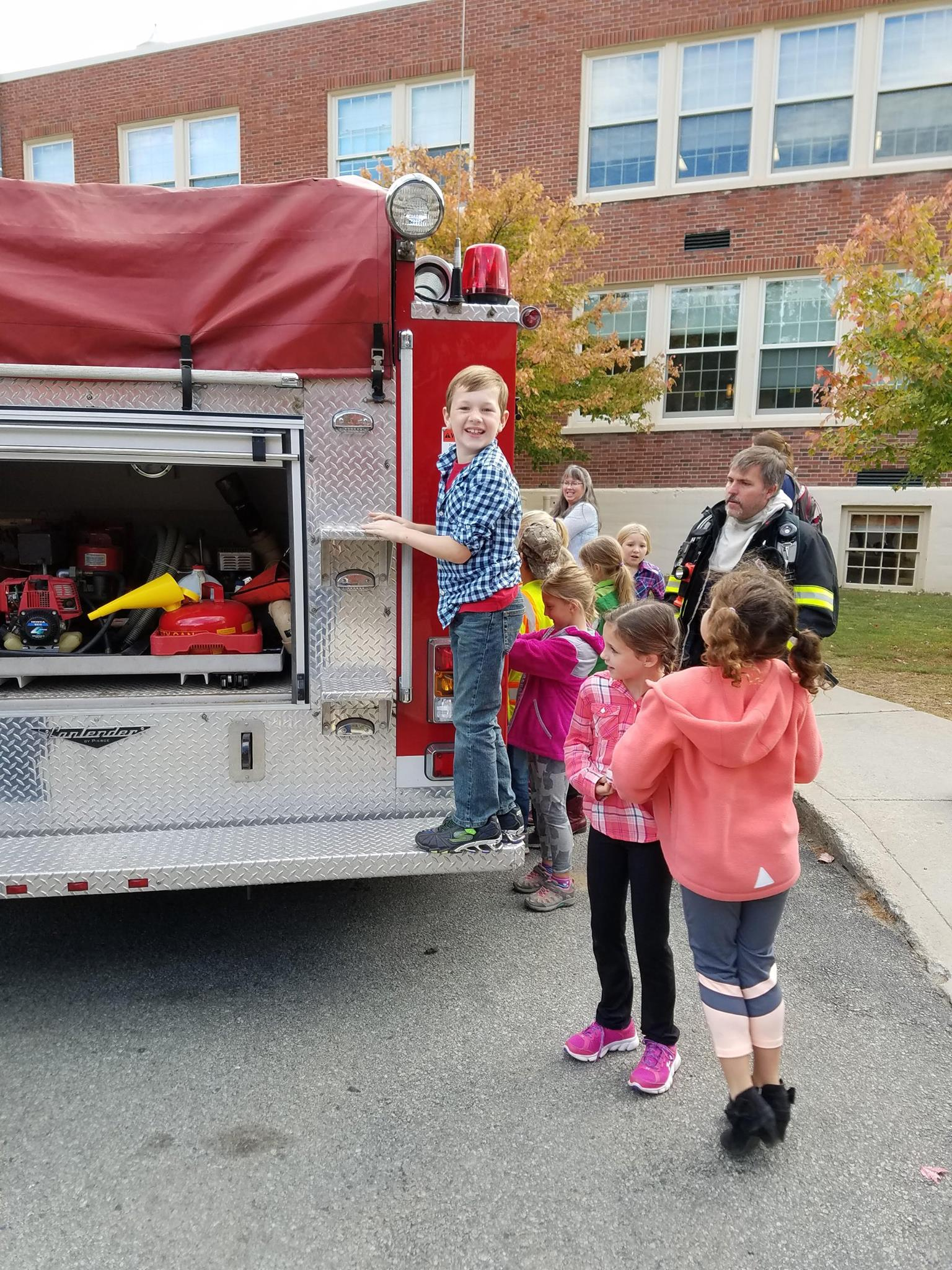 Local students becoming familiar with the fire trucks