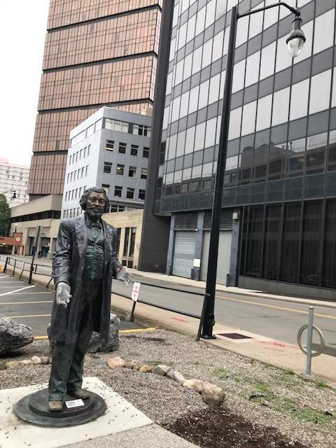 Frederick Douglass sculpture on Corinthian Street in downtown Rochester. - Help us add color, through a yarn intervention at this site, to honor the work of the Rochester Ladies Anti-Slavery Sewing Society, who invited Douglass to speak at Corinthian Hall (now a parking lot) on July 5, 1852, where he delivered his now famous Fourth of July speech.