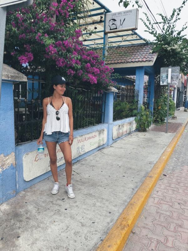 A stylish girl in sports clothes walking on La Quinta Avenida (or Fifth Avenue) in Playa Del Carmen, Mexico