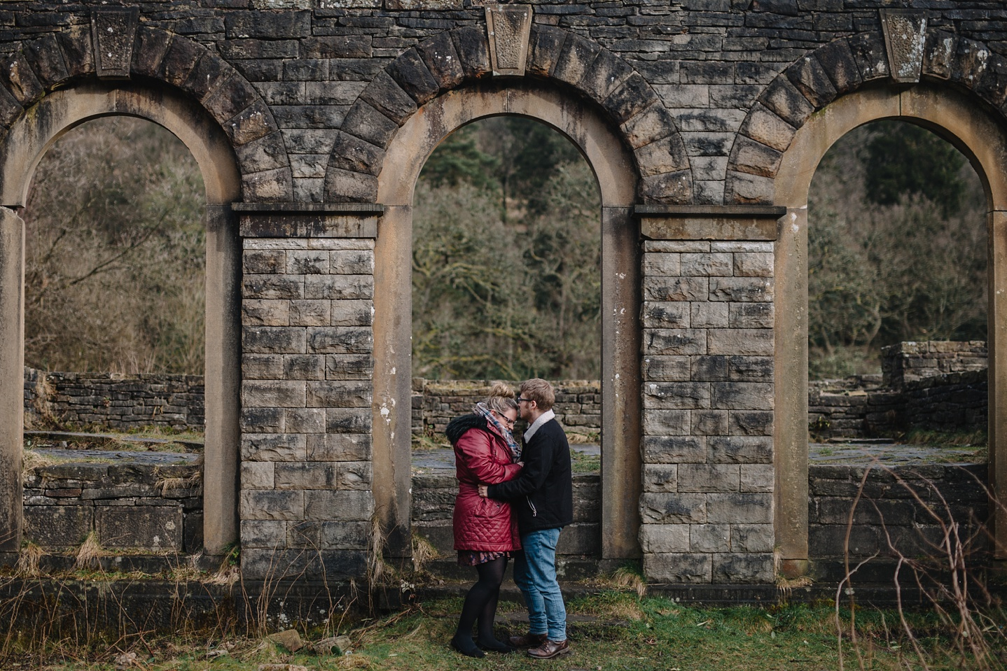 engagement shoot of man and woman cuddling stood infront of the ruin of Errwood Hall