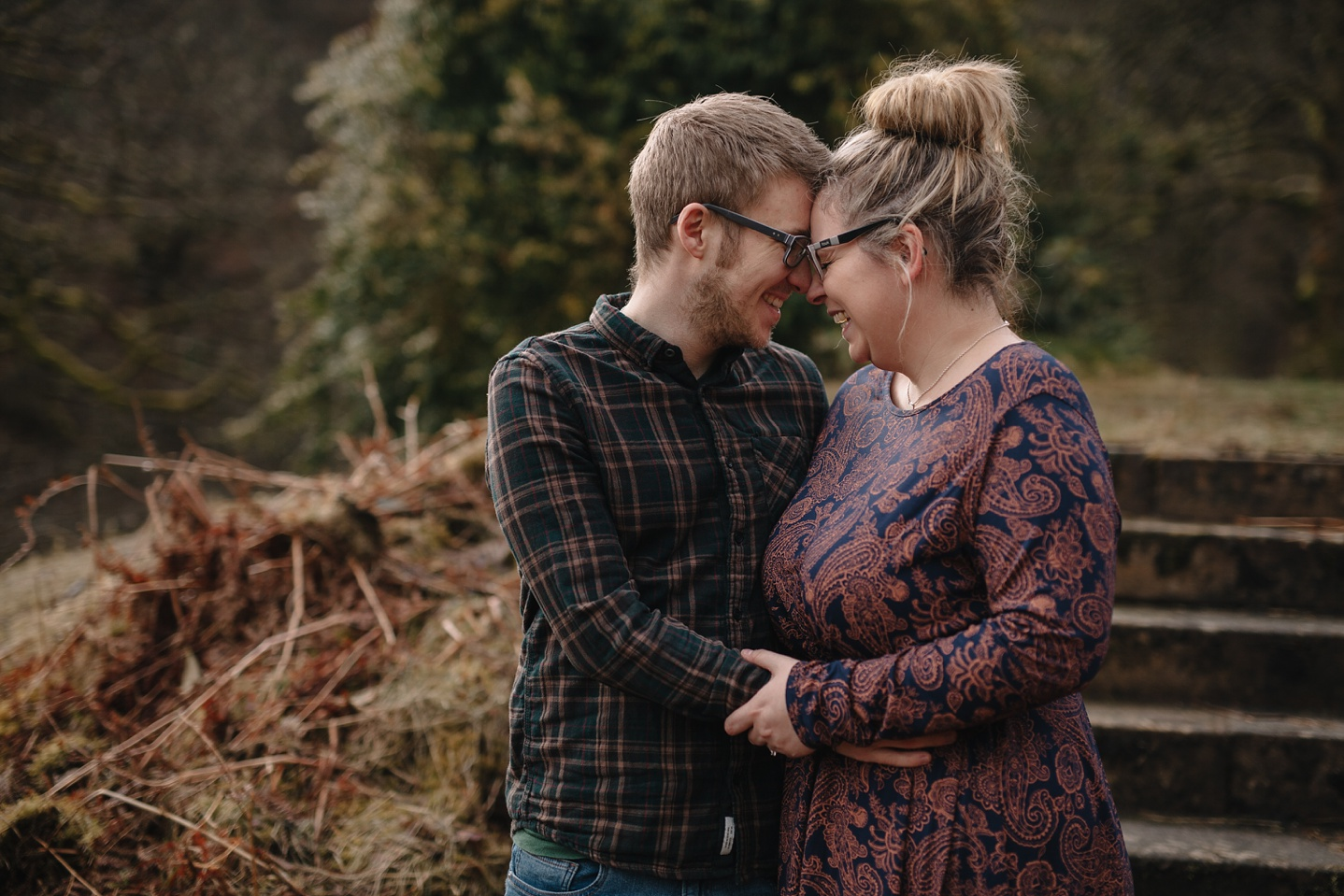 man and woman embracing on the steps of errwood hall
