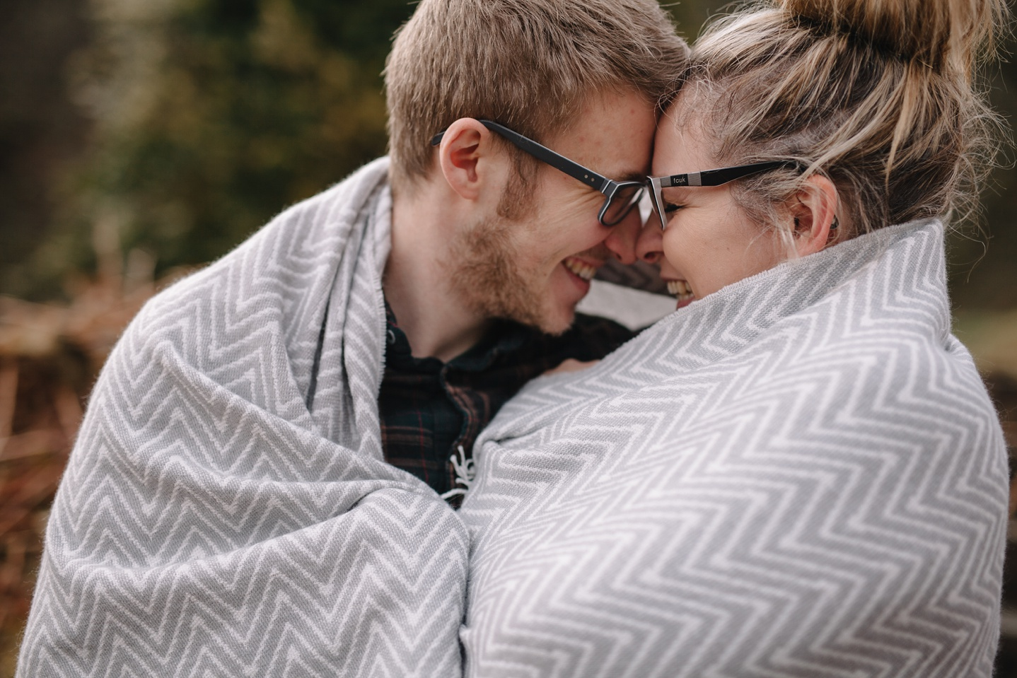 engagement photography of man and woman wrapped up in a grey blanket cuddling