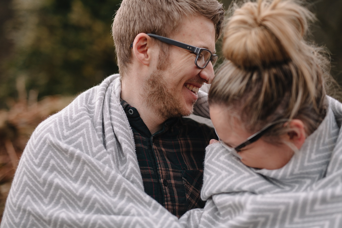 man and woman wrapped in a blanket laughing
