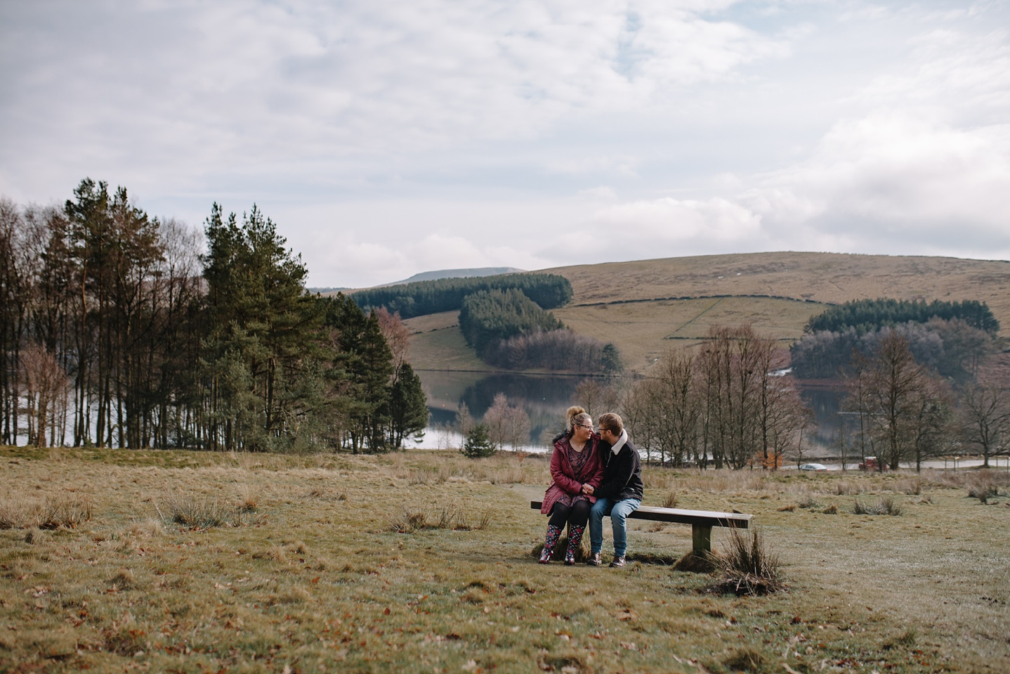 Engagement shoot of man and woman sat on a bench with views of the Goyt Valley